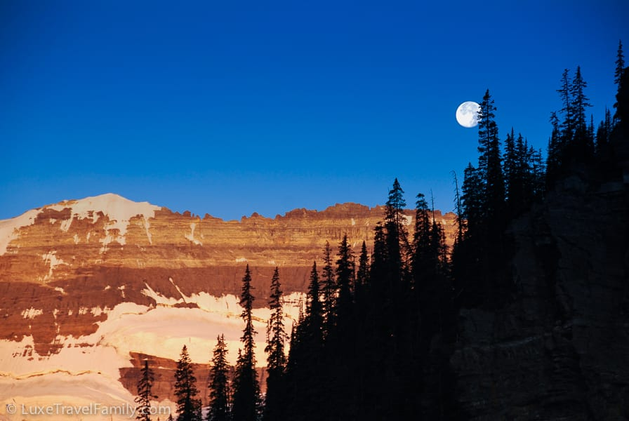 The full moon above Lake Louise sinks lower in the morning sky