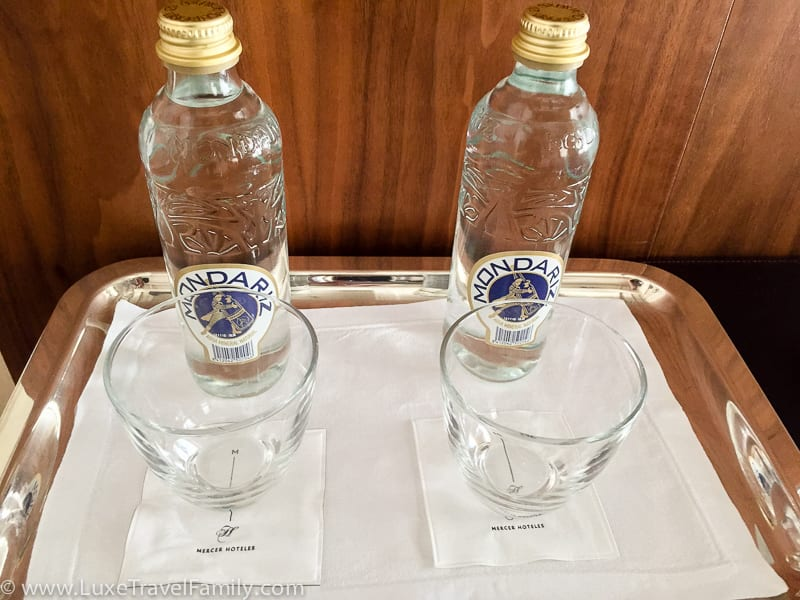 Two glass bottles and glasses in a guest room at the Mercer Hotel Barcelona