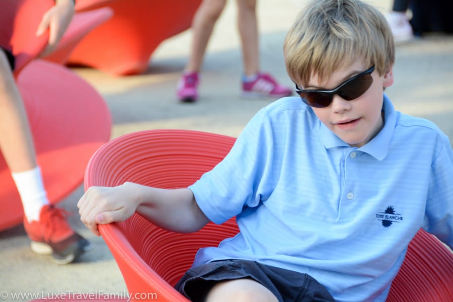 A boy with sunglasses in a red chair that is shaped like a cup at Expo 2015