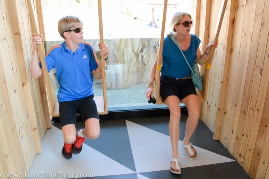 A woman and boy on wooden swings at the Estonia Pavilion, Expo 2015 Milan