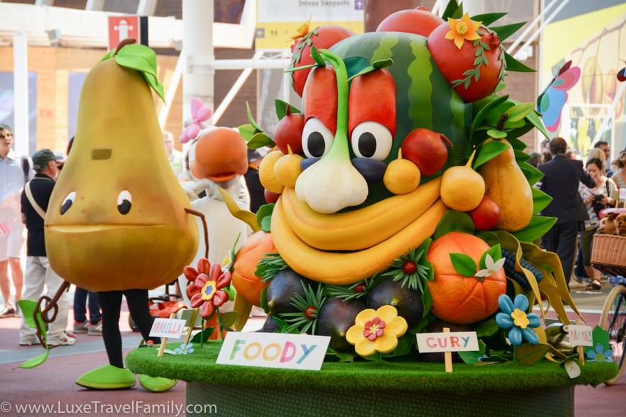 Foody, the Expo 2015 mascot is a colourful creature with two bananas for a mouth and a watermelon for a head.